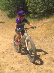 Jessa Freiberg, 8, rides the Princess Ditch Trail in the Swasey Recreation area on May 15.