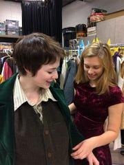 Costume crew member Alison Bishop helps Anna Karius