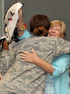 Air Force Sgt. Jackie Vanwagner, left, hugs Carol Edwards after she got a quilt from the Berry Basket Quilters at Medford Leas Community Center in Medford, N.J.