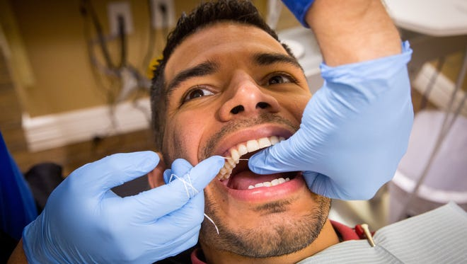Dr. Mathew Petersen, doctor of dental surgery, flosses the teeth of Las Cruces Dental Solutions facility manager Lonnie Bustamante.