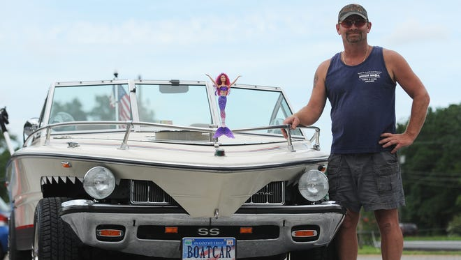 """Reid Diggs stands with his """"Boatcar"""" he built by combining the body of a Stingray boat hull with the frame of a Pontiac car. The Boatcar is completely street legal and passed state inspection. Diggs says he gets plenty of looks and phtotgraphs from people when he's out driving it."""