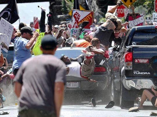 People fly into the air as a vehicle drives into a group of protesters demonstrating against a white nationalist rally on Aug. 12, 2017 in Charlottesville, Va. The nationalists were holding the rally to protest plans by the city of Charlottesville to remove a statue of Confederate Gen. Robert E. Lee. There were several hundred protesters marching in a long line when the car drove into a group of them.