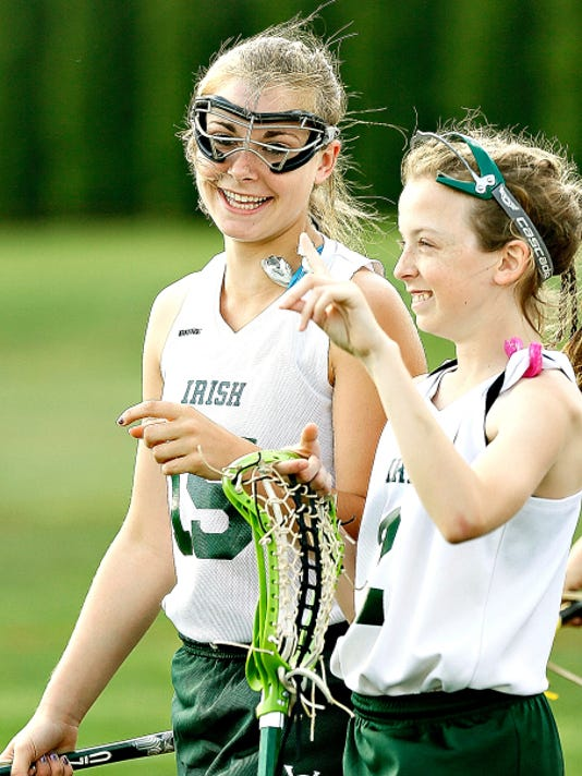 York Catholic High School freshman Sarah Mazzur, 15, back, jokes with  teammate Lauren China, front, during lacrosse pre-game warm-ups at her school  in York, Pa. on Tuesday, May 12, 2015. Mazzur recently won the Herr's Food Inc.'s 'Good Natured Kid Contest', and was awarded a 500.00 scholarship. Dawn J. Sagert - dsagert@yorkdispatch.com