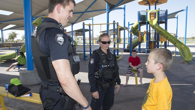 Peoria police Officers Julie Smith and David Ayres talk to Ethan Oxendale, 10, while police go out for community watch at Pioneer Community Park. After a yearlong trial period, Peoria requires all beat officers to wear body cameras to record police interactions with the public.