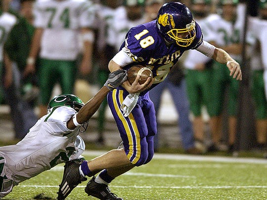 Wylie quarterback Case Keenum (18) tries to shake off a Cuero defender during the Bulldogs' win in the Class 3A Div. I state championship game in December 2004 at Floyd Casey Stadium in Waco.