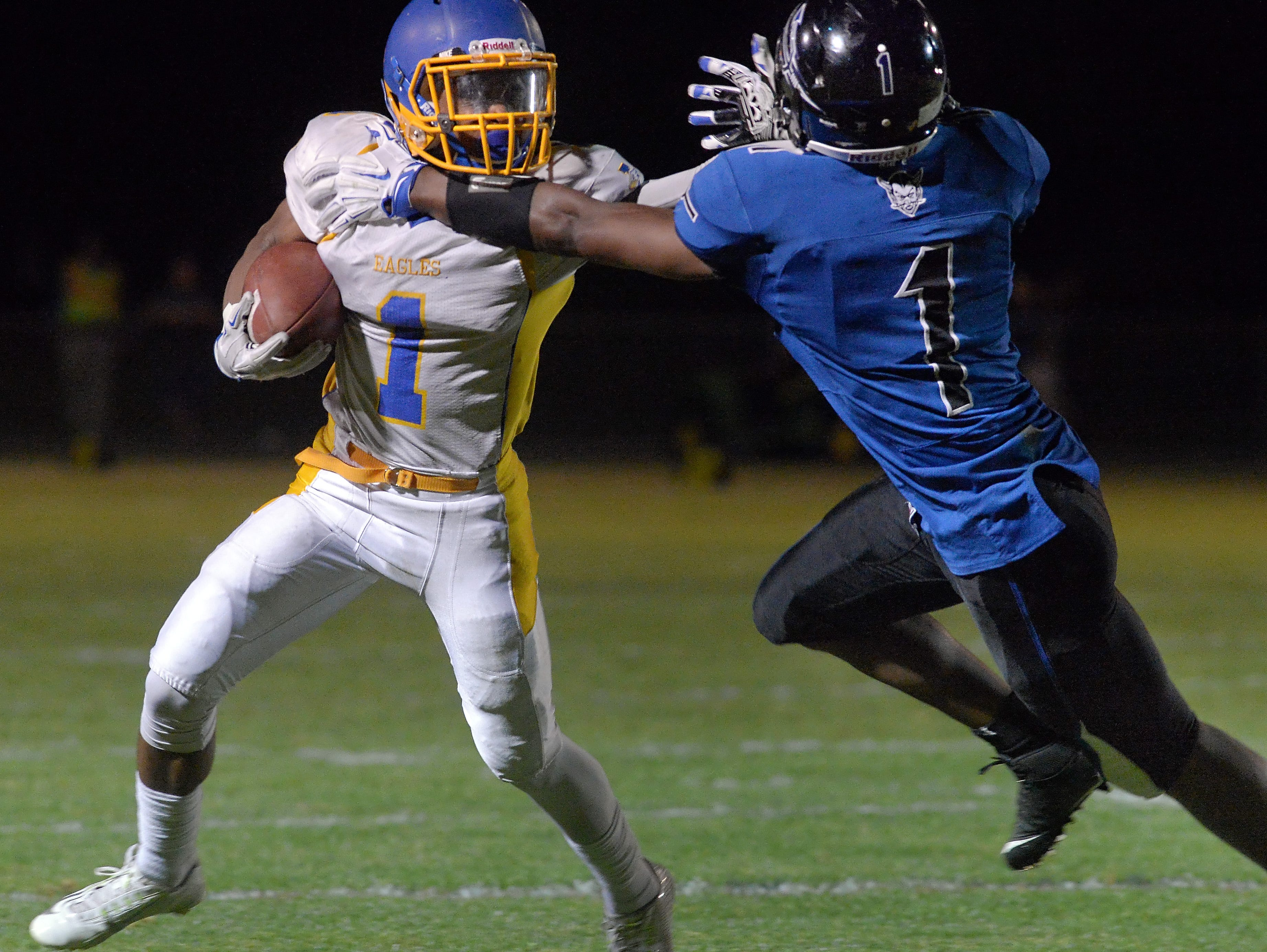 Irondequoit's Fooquan Peace, left, stiff arms Brockport's Cory Gross during a game at Brockport High School on Friday.