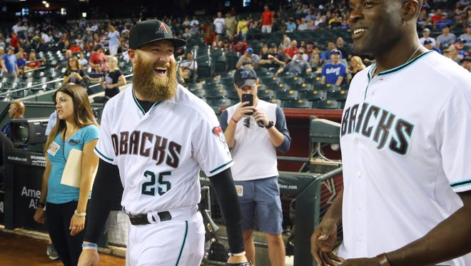 Arizona Diamondbacks relief pitcher Archie Bradley (25) laughs with former Arizona Cardinals defensive end Simeon Rice prior to their MLB game against the Los Angeles Dodgers Tuesday, Aug. 8, 2017, in Phoenix,  Ariz.