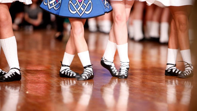 The socks and sandals of two McGing Irish dancers are reflected in the floor of the Music Hall ballroom during the 34th annual Irish Ceili, sponsored by the Cincinnati Irish Cultural Society.