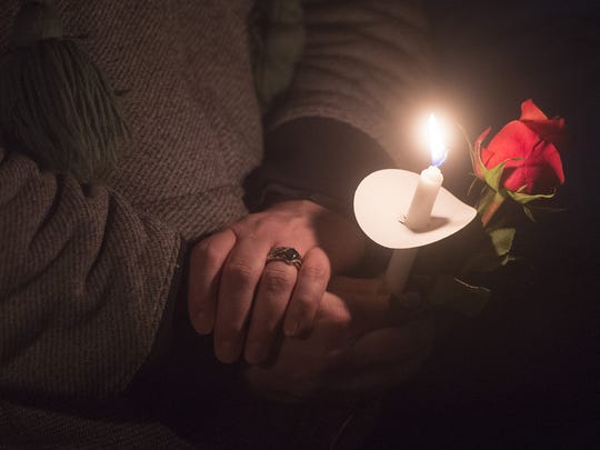 Family and friends of Kimberlee Graves hold flowers as they gather for a candlelight vigil near University Avenue on Friday, January 19, 2018. Graves' body was found January 9 in Lory State Park.