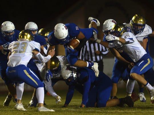 Reno's Brandon Kaho (10) dives through the Reed defense during their football game at Reno on Oct. 13.