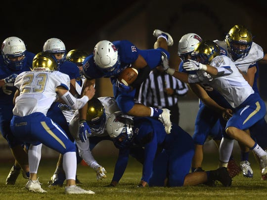 Reno's Brandon Kaho (10) dives through the Reed defense during their football game at Reno on Oct. 13.