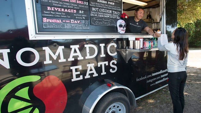 Steven Chang, left, gives regular customer Thu Vo, right, her lunch order during a visit to the mobile food trailer Nomadic Eats Tuesday Oct. 20, 2015. For the past three-years, Nomadic Eats has been located on Underwood Ave. across from Pensacola State College.