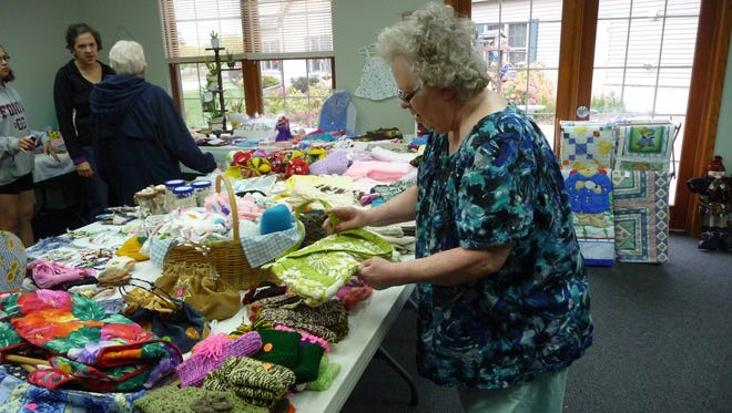 Betty Pinske, admires the handcrafted items made by the residents of Woodlands Senior Park and the Christ Child Society members at last year's event.