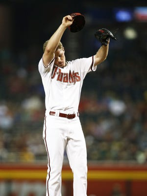 Arizona Diamondbacks pitcher Chase Anderson swipes his brow against the Oakland A's in the 1st inning on Friday, Aug. 28, 2015 at Chase Field in Phoenix, AZ.