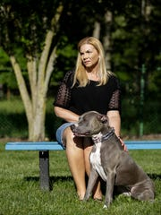 Domestic violence survivor Nicole Beverly of Ypsilanti Township poses for a portrait with her dog Sapphire at Loonfeather Point Park, Thursday, June 1, 2017 in Ypsilanti Township.