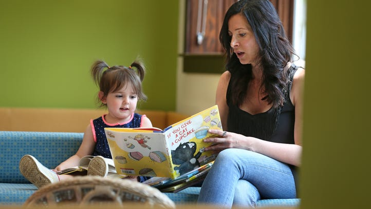 Melissa Nenni, Irondequoit, reads to her daughter Stella DiChiara, 2, in the bright and cheerful Children's Library section at the Irondequoit Public Library on Titus Avenue in Irondequoit Wednesday, May 25, 2016.
