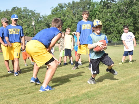 ANI Buckeye Camp Drew Tyson (right) practices a spin move at the Buckeye Youth Football Camp held Tuesday, June 23, 2015.-Melinda Martinez/The Town Talk