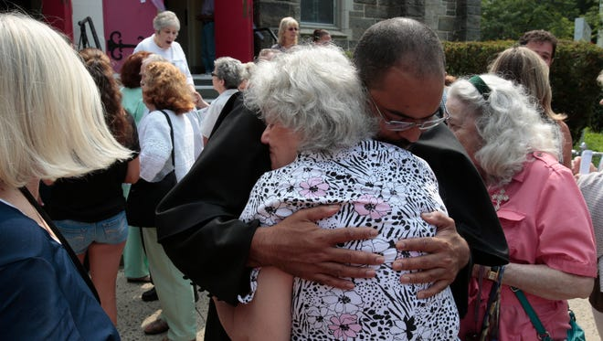 Fr. Jean-Paul Soler, Poster of St. Denis Church in Yonkers hugs a congregation members after a mass on July 26, 2015.