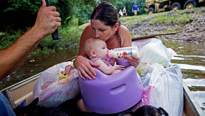 Danielle Blount kisses her 3-month-old baby, Ember, as she feeds her and wait to be rescued from floodwaters by members of the Louisiana Army National Guard near Walker in August