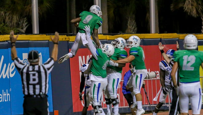 The Argos celebrate after Ka'Ron Ashley (9) scores a touchdown against Chown University in the first home game of the 2017 season at Blue Wahoos Stadium on Saturday, Sept. 16, 2017.