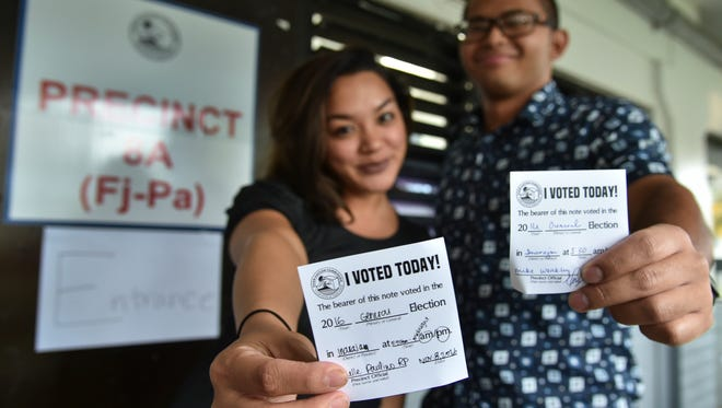 "Gianna Mesa, left, and John Camacho Jr. show thier voting swag shortly after casting their ballots at Inarajan Middle School on Nov. 8. ""I voted because I care about my island, and I hope that my vote makes Guam a better place to live,"" said Mesa."