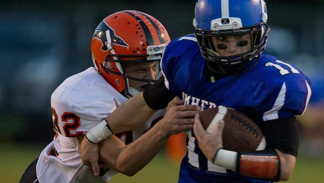Amherst's Dalton Nemzoff, right, tries to evade Iola-Scandinavia's Jalen Block, left, during their Central Wisconsin Conference game at Amherst High School on Friday, Sept. 4, 2015. Iola-Scandinavia and Amherst are still alive in the prep football playoffs.