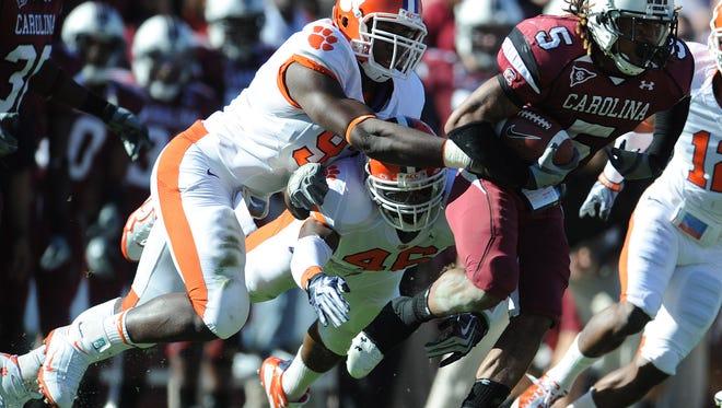 South Carolina QB Melvin Ingram (5) and linebacker Jonathan Willard (46) carries past Clemson defensive end Malliciah Goodman (97) during the second quarter Saturday, November 28, 2009 at Carolina's Williams Brice Stadium in Columbia.