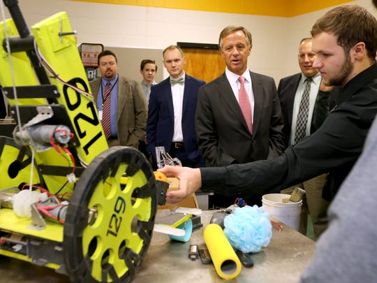 Tennessee Governor Bill Haslam center listens to Central Magnet High School sophomore Aidan Gibson right, explain their robot project as Haslam tours the school, on Wednesday, Jan. 25, 2017.