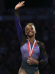 Trinity Thomas waves to fans after winning third place of the senior floor exercise during senior women's opening round of the U.S. gymnastics championships, Sunday, Aug. 20, 2017, in Anaheim, Calif. (AP Photo/Ringo H.W. Chiu)