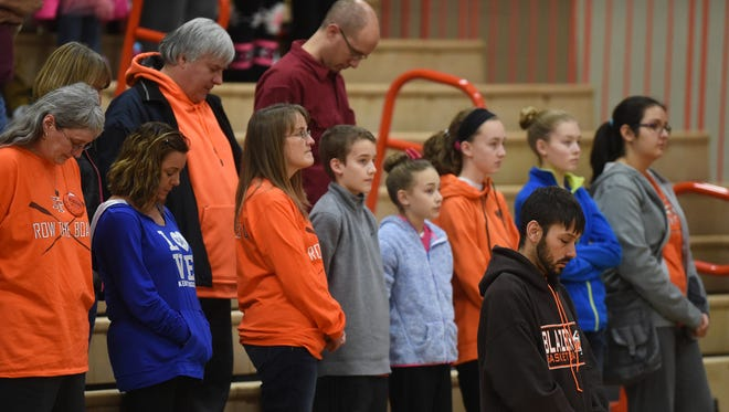 Audience members stand for a moment of silence to remember Olivia Starr Wallace, 16, before a basketball game between National Trail and Lincoln Tuesday, Jan. 10, 2017, in New Paris, Ohio.