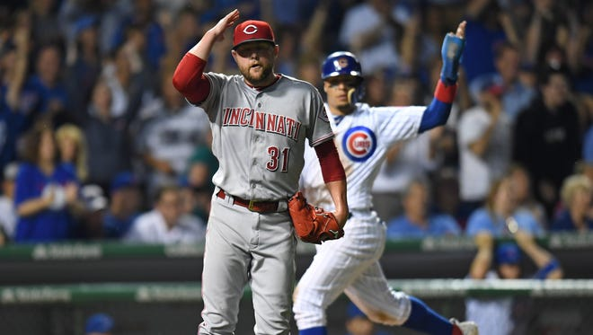 Aug 14, 2017; Chicago, IL, USA; Cincinnati Reds relief pitcher Drew Storen (31) reacts as Chicago Cubs second baseman Javier Baez (behind) runs in to score in the seventh inning at Wrigley Field. Mandatory Credit: Patrick Gorski-USA TODAY Sports
