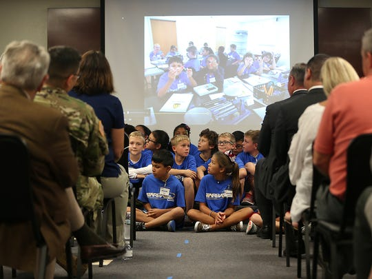 Fifth graders from Santa Rita Elementary sit in front of a screen displaying a slideshow of photos of them learning STEM curriculum as part of the base's newly implemented STARBASE program Oct. 4. 2017.