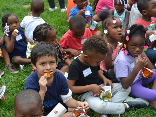 Children eat snacks at the Mariano Rivera Foundation's backpack giveaway in Wilmington's Rodney Square last year.