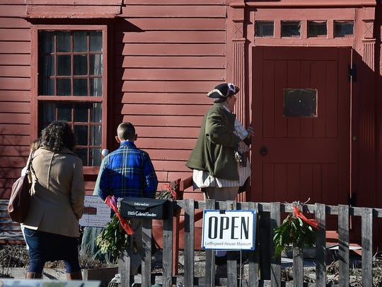 Art Mueller, right, a volunteer at the Leffingwell House Museum in Norwich, Conn., enters the front door during the annual 2016 Leffingwell Colonial Christmas Sunday, Dec. 4, 2016.