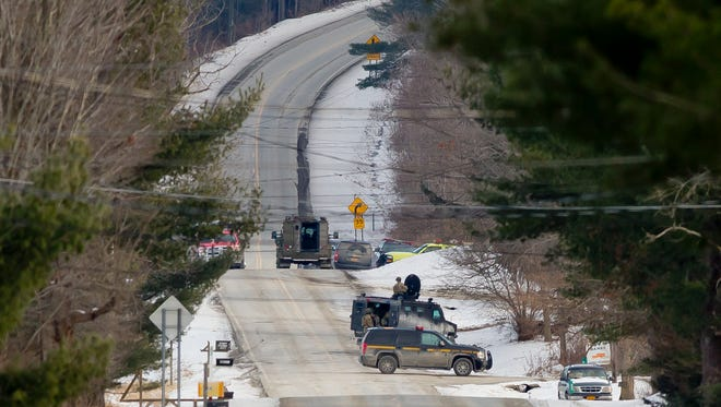 Police officers in tactical gear work Thursday morning on Hornbrook Road in Danby as a standoff with a man barricaded inside a home continues.