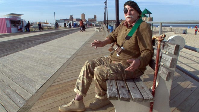 Douglas Berry plays his backpacking guitar on the Asbury Park boardwalk. With a Tom Waits kind of shtick, Berry is a poet who is a staple of the spoken word circuit at the Shore.