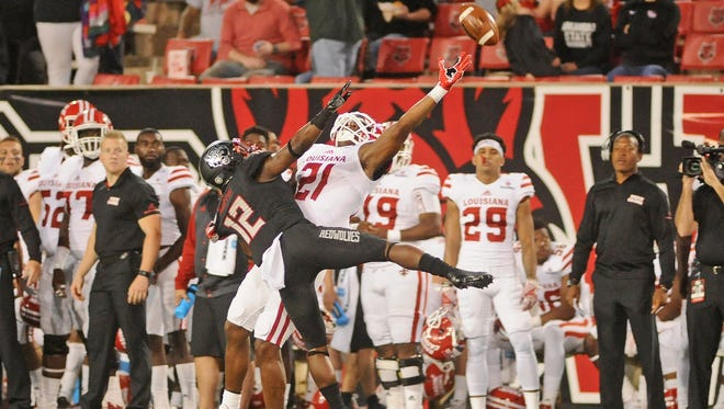 UL wide receiver Keenan Barnes tries to catch a pass, but a flag is called on Arkansas State's defensive back Kyle Martin during the first half of Thursday's game at Centennial Bank Stadium in Jonesboro, Arkansas.