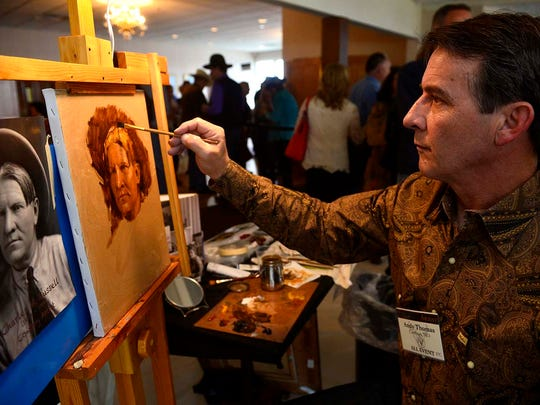 "Andy Thomas works on ""Charlie"" during an art event in Great Falls, Montana, in this 2014 photo. Thomas is known for his Western paintings."