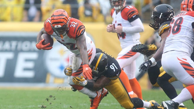 Cincinnati Bengals running back Jeremy Hill (32) caries the ball as Pittsburgh Steelers defensive end Stephon Tuitt (91) defends during the first quarter at Heinz Field.