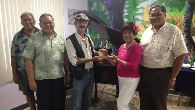 Asmuyao Community School Director Rand Coffman presents a plaque to the Lamorena siblings Friday at the school. The plaque will be placed on the piano to commemorate their donation.