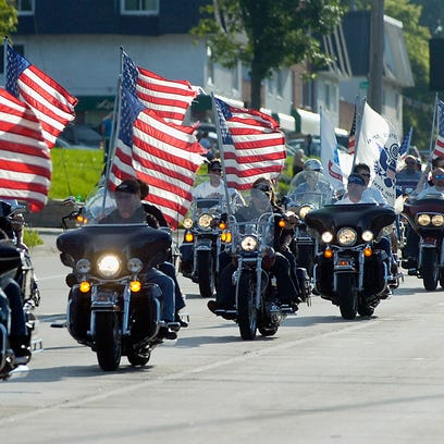 Riders carrying American Flags lead a parade of thousands