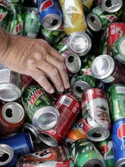 Dave Arndt of Menasha feeds aluminum cans into the
