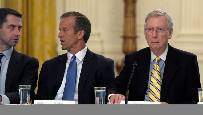 Senate Majority Leader Mitch McConnell of Ky., right, seated next to Sen. Tom Cotton, R-Ark., left, and Sen. John Thune, R-S.D., center, waits for President Donald Trump to join a meeting of Republican senators on health care in the East Room of at the White House in Washington, Tuesday, June 27, 2017.