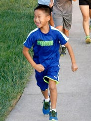 Micah Lu, 7, enjoys running with his family. He will