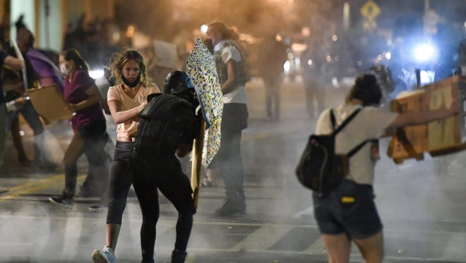 Protesters stand amid clouds of chemical irritant released by police outside police headquarters in Rochester, N.Y., Thursday night.