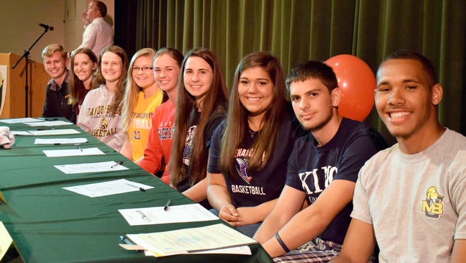 Wilson Memorial High School on Thursday celebrated its annual signing day as nine student-athletes officially announced the college choices. From right, Greg Woodard, Justin Stewart, Sarah Sondrol, Hannah Johnson, Emilie Miller, Morgan Hughes, Cheridan Hatfield, Olivia Farley and Ryan Aud.