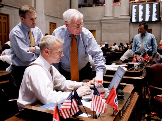 Rep. Bill Dunn, R-Knoxville, left, and Rep. Charles Sargent, R-Franklin, right, look on as Rep. Jon Lundberg, R-Bristol, seated, works on his computer during a House session on May 21, 2008.
