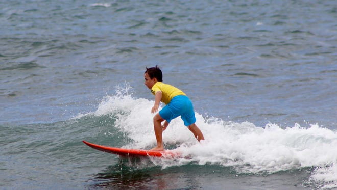 Guam surfer Campbell Starley, 9, rides a wave during the 40thannual Menehune Surf Contest held on the North Shore of Oahu, Hawaii on Oct. 15 and 16.