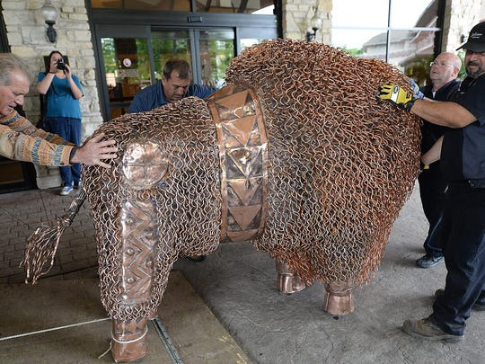 "A life-size copper bison is unloadedJune 5 at the Radisson Hotel and Conference Center. Oneida artist Mark Fischer, left, created this sculpture to help promote Native American awareness and named it ""Ancient Dignity."" The 1,200-pound sculpture will be on public display at the Oneida Nation's Radisson Hotel and Conference Center as part of the Woodland Indian Art Show & Market this weekend."
