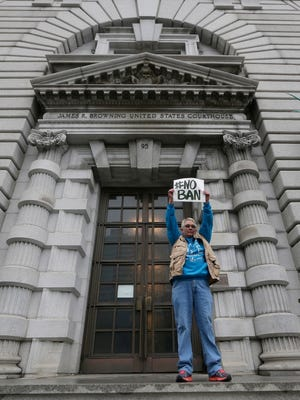 A lone protester holds a sign in February protesting President Trump's travel ban outside the 9th U.S. Circuit Court of Appeals in San Francisco.